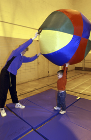 Student and teacher playing with large ball