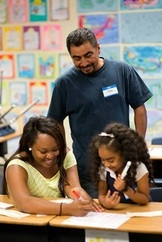 Adult male volunteer standing over a teacher working with a student on a school assignment