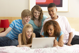Group of students with a laptop sitting on a couch in home environment
