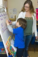Teacher assistant at easel with preschool student.