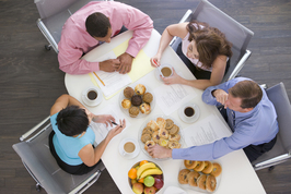 Aerial photo of group of adults meeting at conference table with breakfast food during the meeting.
