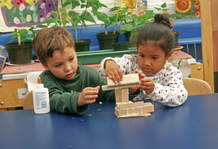 Two preschool children glueing shapes together