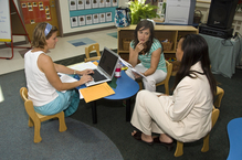 Teachers meeting at a conference table with computers and papers on table.