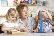 Preschool teacher with two preschool students playing with stacking toy.