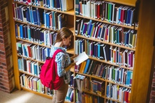 High school student looking at book in library book stacks