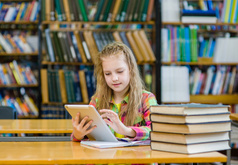 Girl sitting at library table surrounded by books and holding an electronic tablet.