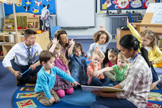 Group of preschool students sitting on carpet with teacher during story time