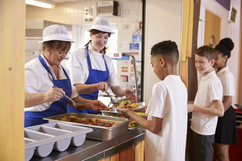 School cafeteria workers serving students lunch