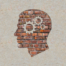 Human head profile with gears and cogs inside the head, brick wall background