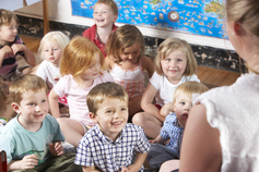 preschool children sitting on classroom floor listening to teacher