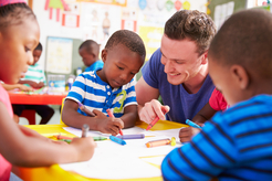 Male preschool teacher working at table with three students