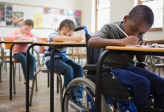 Student in wheelchair working at his desk in school