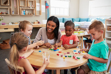 Preschool teacher working at table with group of preschool students