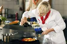 Young female chef cooking at stove using cast iron skillet