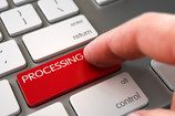 Finger on computer keyboard pressing PROCESSING key