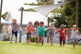 Preschool children running outside.