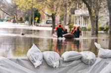 Sand bags, people in boat on flooded street.