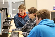 Students conferring around a computer.