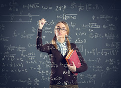 Female high school student standing at large see thru board working on math problem.