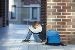 student seated leaning against outside of building, head down