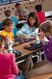 Students eating at tables in school cafeteria