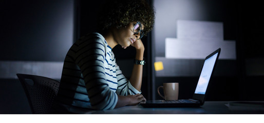 stressed student in front of computer at night with a cup of coffee