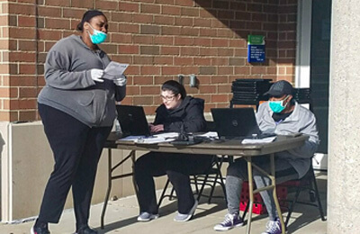 Station set up outside a school for students to receive Chromebooks.