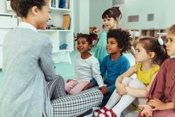 Preschool children listening to teacher read a story.