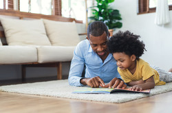 African-American father with preschool child, reading a book.