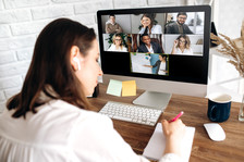 Woman sitting at desk in front of a computer with screen showing others participating in a Zoom meeting.