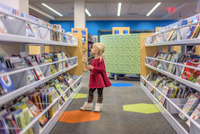 Preschool girl looking at books in library.