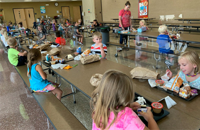 Children eating lunch in school cafeteria with clear dividers separating them.