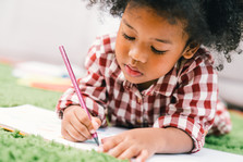 African American preschool girl with pencil and paper.