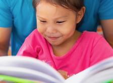 Preschool girl reading.