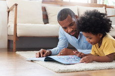 Adult male reading with preschooler