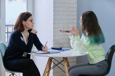 Adult speaking with high school student
