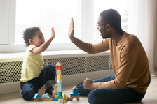 African American male childcare provider with a child.