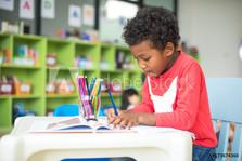 Preschool boy writing at desk.