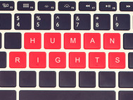 "A laptop keyboard with ""Human Rights"" showing on the keys."