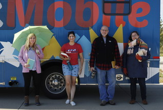 Four people in clothing for every season in front of the bookmobile