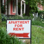 A for rent sign is shown in a yard.