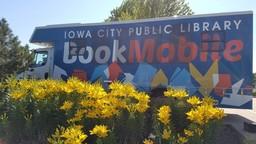 ICPL Bookmobile behind yellow flowers