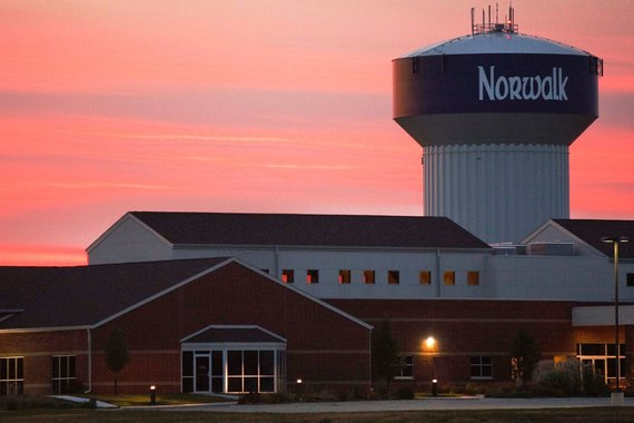 A sunset view of the Norwalk water tower behind St. John's church