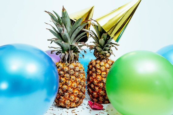 pineapples in party hats with sunglasses and balloons