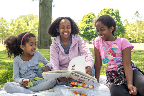 mom and girls in park with book