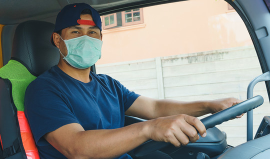 Man driving truck wearing mask