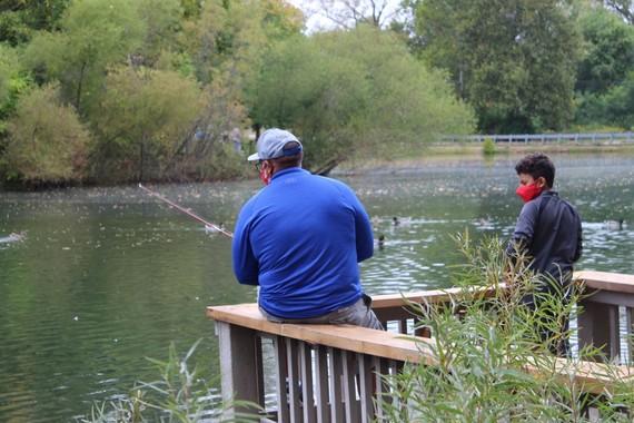 Older man and younger boy at Krannert Park fishing off dock