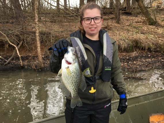 Fisheries biologist holding up crappie in boat