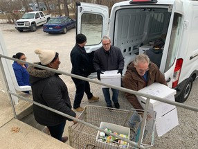 Indiana Housing and Community Development Authority (IHCDA) employees loading a van with donations