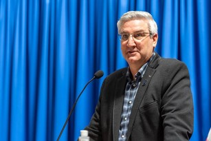 Governor Eric Holcomb speaking to a microphone
